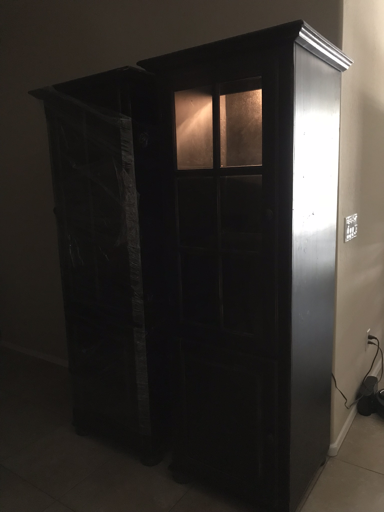 Two large Black Distressed bookcases with lights and glass doors.